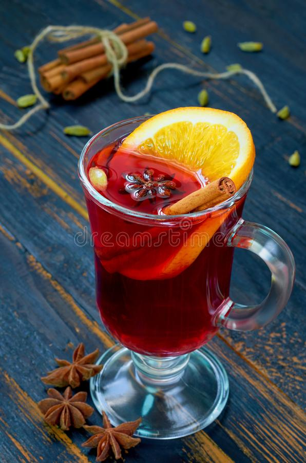 Glühwein mit orange Scheiben- und Wintergewürzen - Zimt-, Kardamom- und Anissterne auf dem schwarzen hölzernen Hintergrund lizenzfreies stockbild
