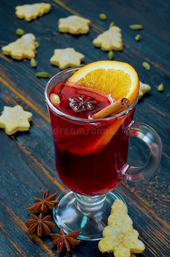 Glühwein mit orange Scheiben- und Wintergewürzen - Zimt-, Kardamom- und Anissterne auf dem schwarzen hölzernen Hintergrund stockfotos