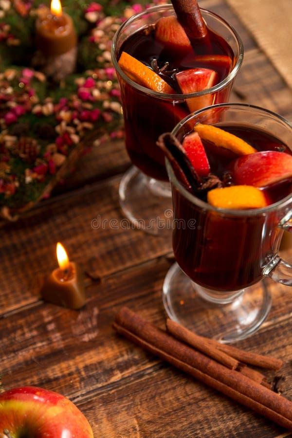 Glühwein nahe Kerze mit Früchten und Gewürzen auf Holztisch Weihnachten GETRÄNK-Rezeptbestandteile des Winters Erwärmungsherum Cu lizenzfreie stockfotografie