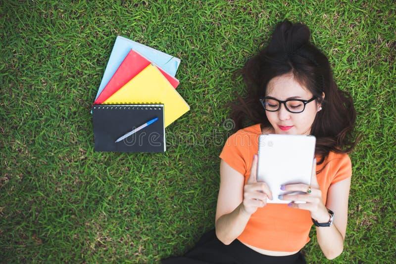 Gl?ckliche Asiatin, die Tablette bei der Entspannung im Park verwendet Leute und Lebensstilkonzept Technologie- und Entspannungst stockbild
