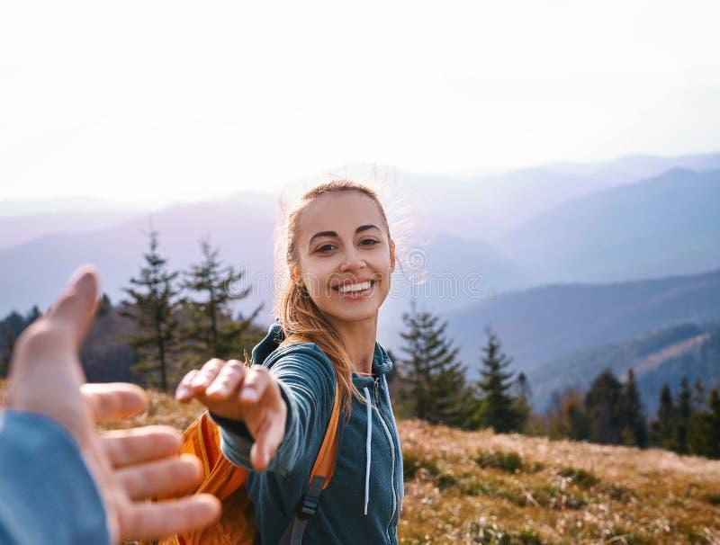 Gl?ckliche attraktive Frauenwandererstellung auf dem Berghang gegen Hintergrund des Sonnenuntergangs Reisen und Follow-me stockfoto