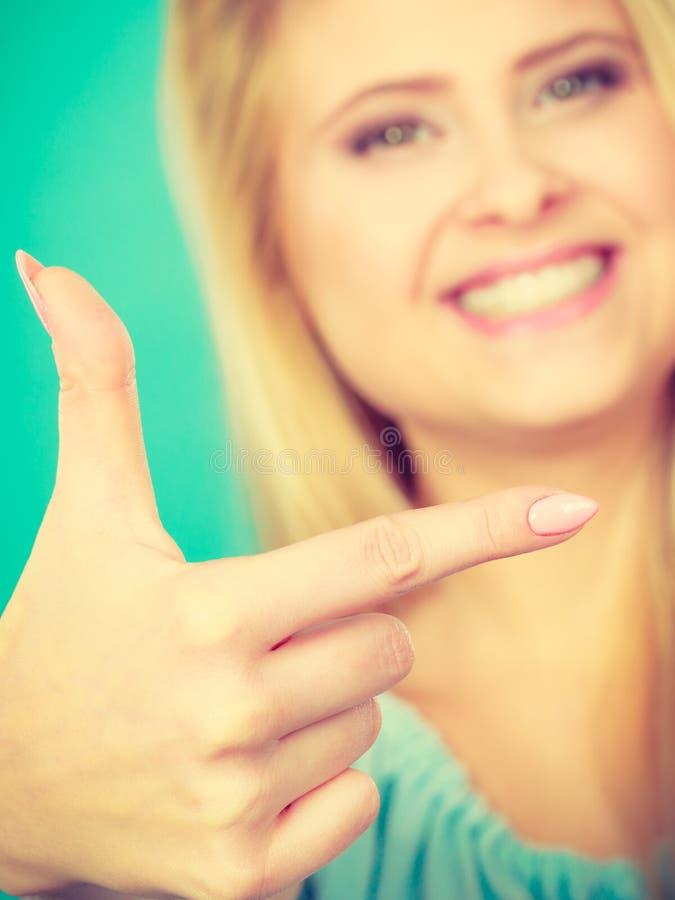 Gl?ckliche Blondine, die mit einem Finger zeigen stockfotografie