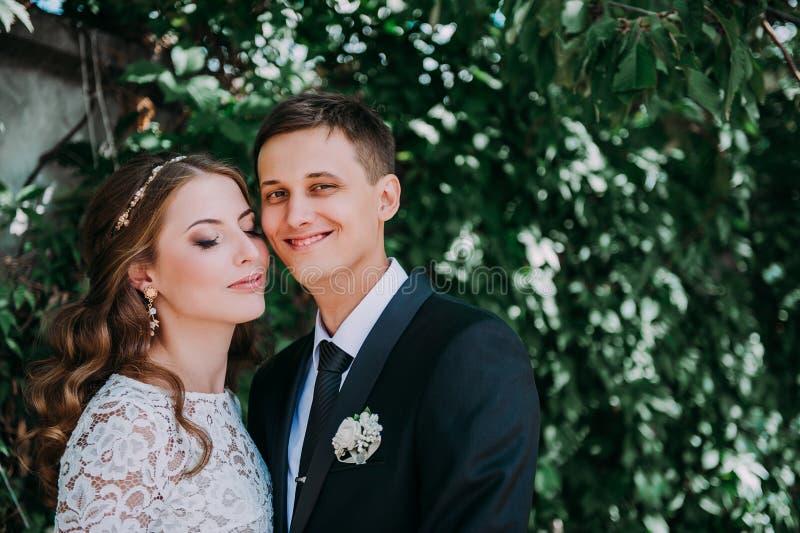 Gl?ckliche Braut und Br?utigam an einem Park an ihrem Hochzeitstag lizenzfreies stockfoto