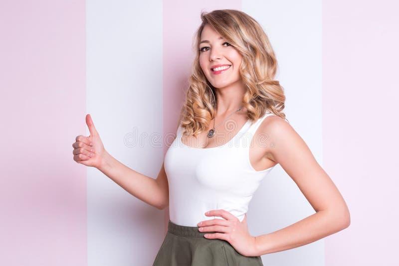 Gl?ckliche emotionale Frau, die Daumen oben auf rosa Hintergrund aufwirft und zeigt Junge Blondine, die Daumen, genehmigend aufge lizenzfreie stockbilder