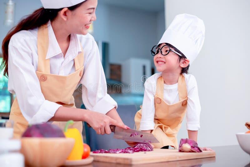 Gl?ckliche Familie in der K?che Unterrichtender Sohn der Mutter für gesunde Nahrung des Kochs stockfotos
