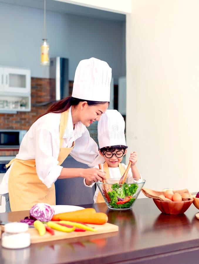 Gl?ckliche Familie in der K?che Unterrichtender Sohn der Mutter für gesunde Nahrung des Kochs lizenzfreies stockfoto