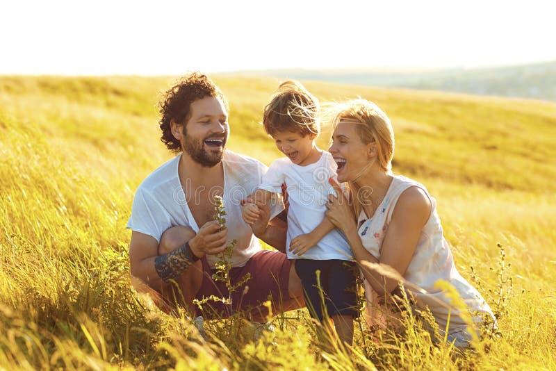Gl?ckliche Familie, die den Spa? spielt auf dem Gebiet hat lizenzfreie stockbilder