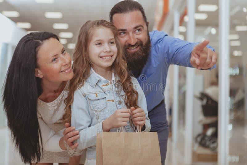 Gl?ckliche Familie, die im Einkaufszentrum zusammen kauft stockfotografie
