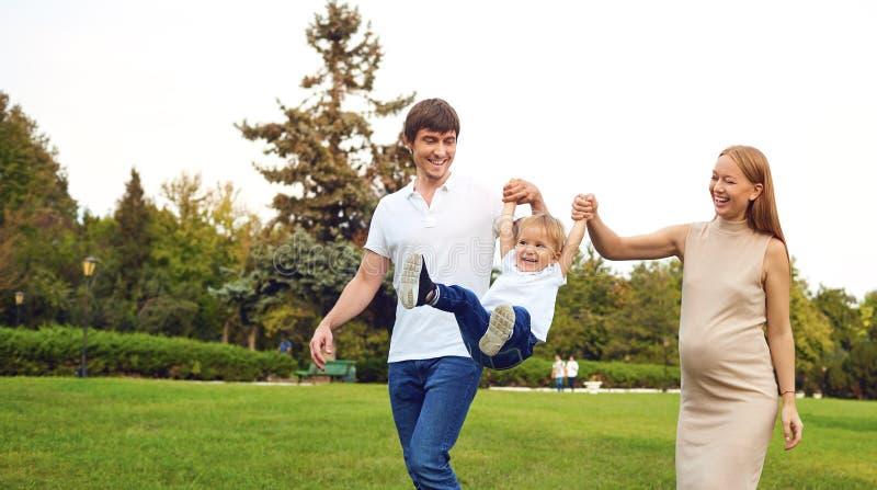 Gl?ckliche Familie, die mit Baby im Park spielt stockfotos