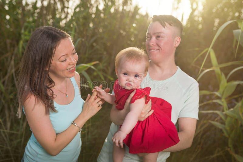 Gl?ckliche Familie im Parkabendlicht Die Lichter einer Sonne Gl?cklicher Weg der Mutter, des Vatis und des Babys bei Sonnenunterg lizenzfreie stockfotografie