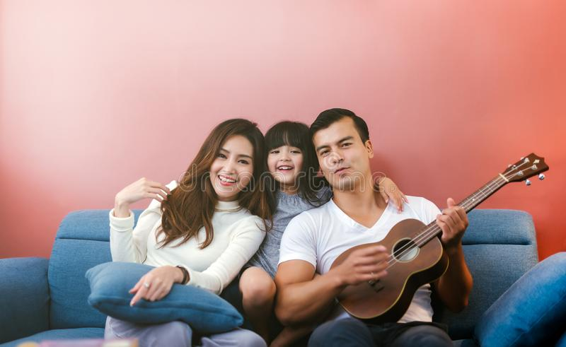 Gl?ckliche Familie mit Gitarre zu Hause Elternteil sehen Tochter, Gitarre zu spielen lizenzfreie stockfotos