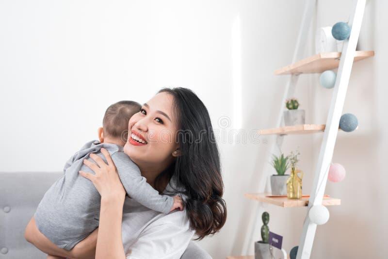 Gl?ckliche Familie zu Hause Bemuttern Sie das Halten der Babytochter im Wohnzimmer am gem?tlichen Wochenendenmorgen stockbilder
