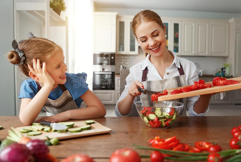 Gl?ckliche Familienmutter mit dem Kinderm?dchen, das Gem?sesalat zubereitet stockfoto