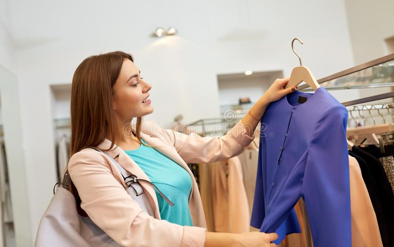 Gl?ckliche Frau, die Kleidung am Bekleidungsgesch?ft w?hlt lizenzfreie stockbilder