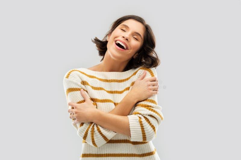 Gl?ckliche Frau im gestreiften Pullover, der sich umarmt stockfoto