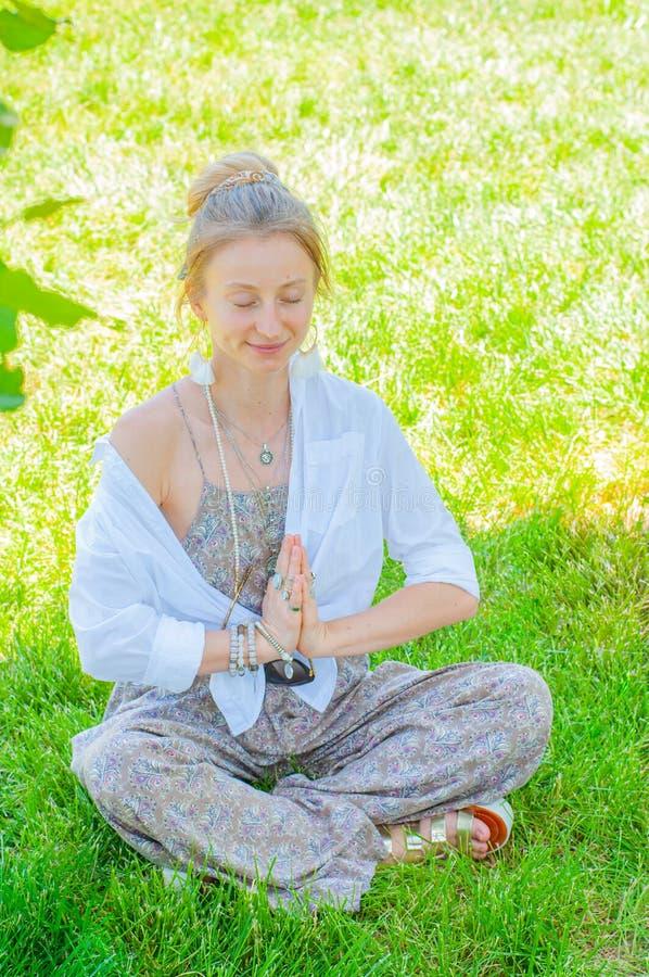 Gl?ckliche Frau ist meditierendes Sitzen in Lotus-Haltung auf Gras Sch?ne boho Artfrau mit Zus?tzen sonnigen Tag im Park genie?en lizenzfreie stockfotos