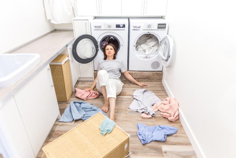 Gl?ckliche Frauenhausfrau in der Waschk?che nahe der Waschmaschine mit schmutziger Kleidung lizenzfreies stockbild