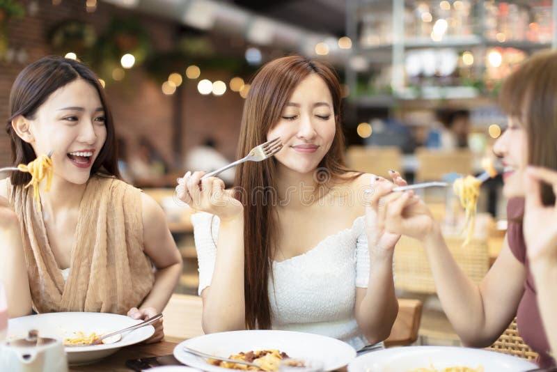 Gl?ckliche Freunde, die im Restaurant zu Abend essen lizenzfreie stockfotografie