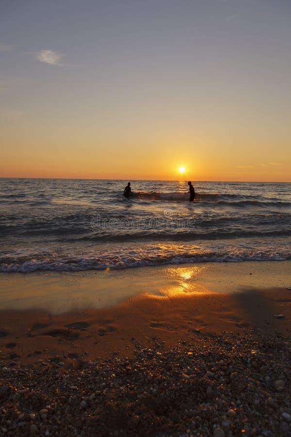 Gl?ckliche Freunde am Sonnenuntergangseestrand lizenzfreies stockbild