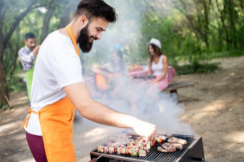 Gl?ckliche Freunde, welche die Grill- und Grillpartei im Freien genie?en stockbild