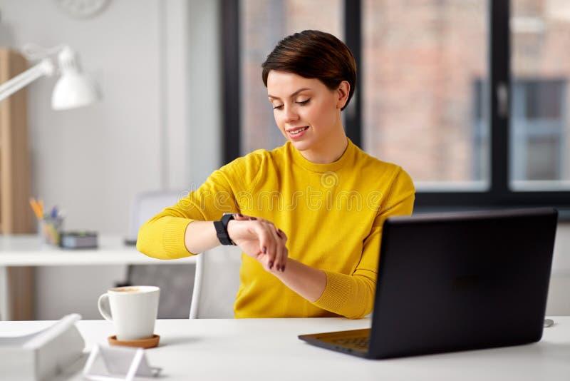 Gl?ckliche Gesch?ftsfrau, die intelligente Uhr im B?ro verwendet lizenzfreie stockfotografie
