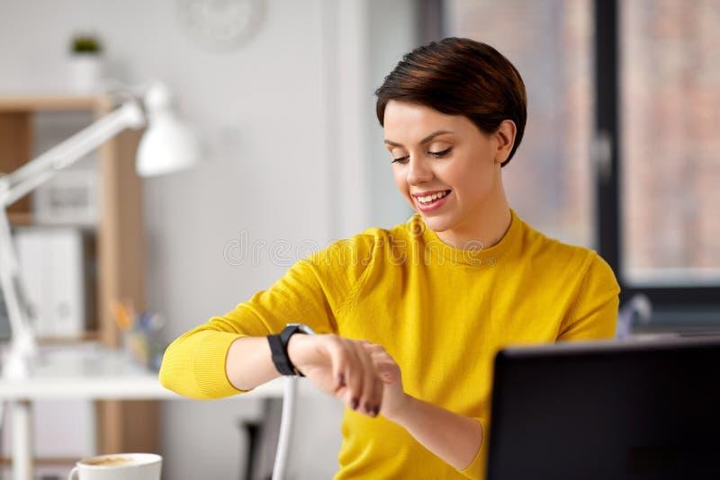 Gl?ckliche Gesch?ftsfrau, die intelligente Uhr im B?ro verwendet stockfotos