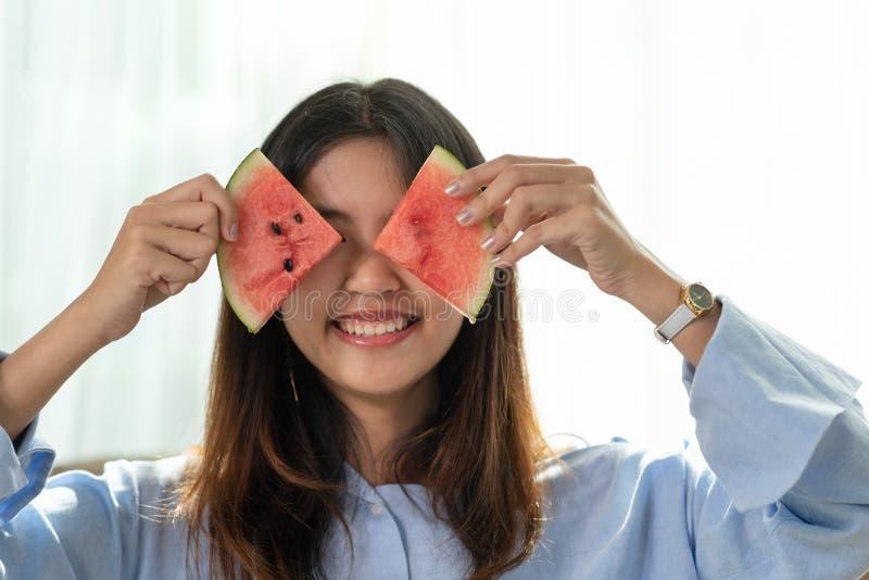 Gl?ckliche junge asiatische Frau des Portr?ts h?lt Scheibe der Wassermelone stockfotos
