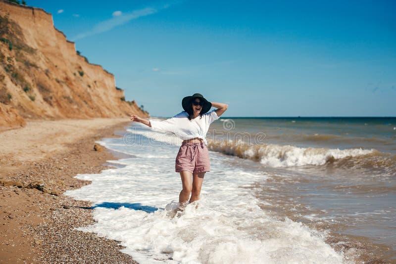 Gl?ckliche junge boho Frau, die Spa? in den Meereswellen am sonnigen warmen Tag auf Tropeninsel geht und hat Krasnodar Gegend, Ka lizenzfreies stockbild