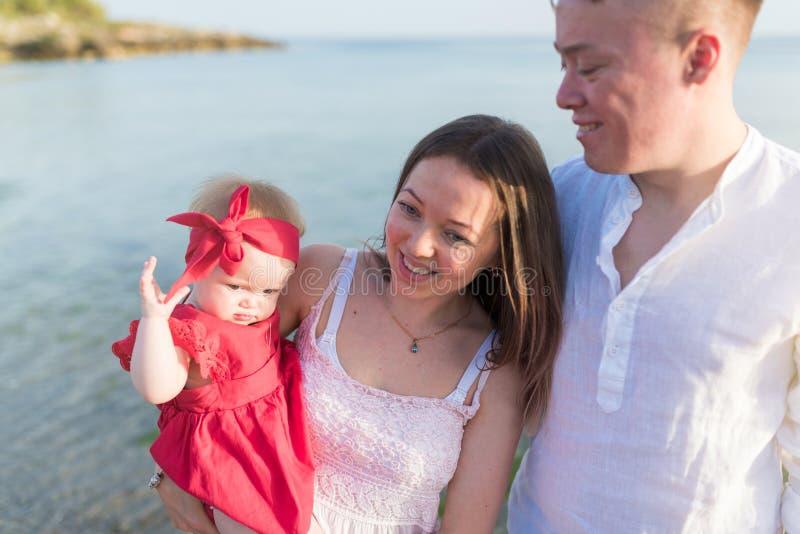 Gl?ckliche junge Familie an der K?ste Mutter hält ihre kleine Tochter lizenzfreie stockfotos