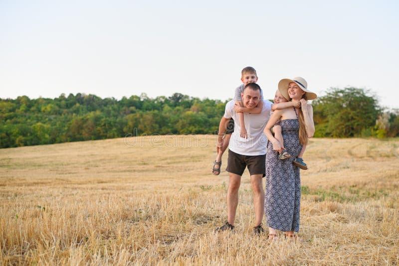 Gl?ckliche junge Familie Ein Vater, eine schwangere Mutter und zwei wenige S?hne auf ihren R?ckseiten Abgeschr?gtes Weizenfeld au lizenzfreies stockbild