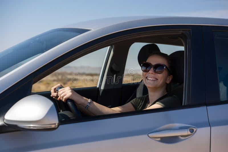 Gl?ckliche junge Frau, die ein gemietetes Auto in der W?ste von Israel f?hrt stockfotos