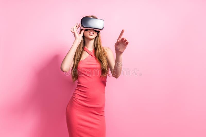 Gl?ckliche junge Frau, die einen Kopfh?rer der virtuellen Realit?t verwendet lizenzfreie stockfotografie
