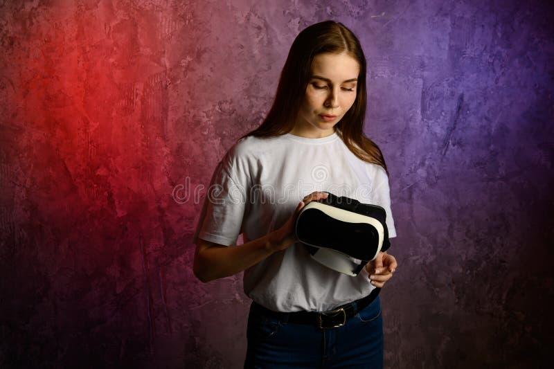 Gl?ckliche junge Frau, die einen Kopfh?rer der virtuellen Realit?t verwendet stockfotos