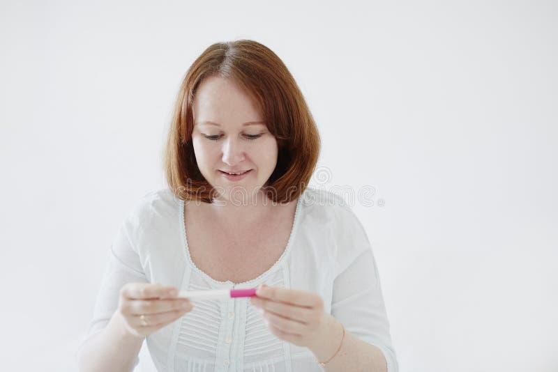 Gl?ckliche junge Frau, die positiven Schwangerschaftstest betrachtet stockbild