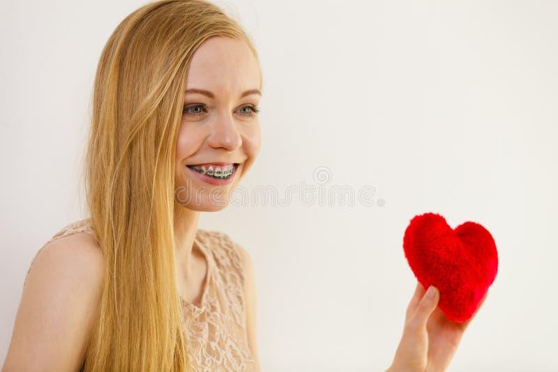 Gl?ckliche junge Frau, die rotes Herz h?lt stockfotografie