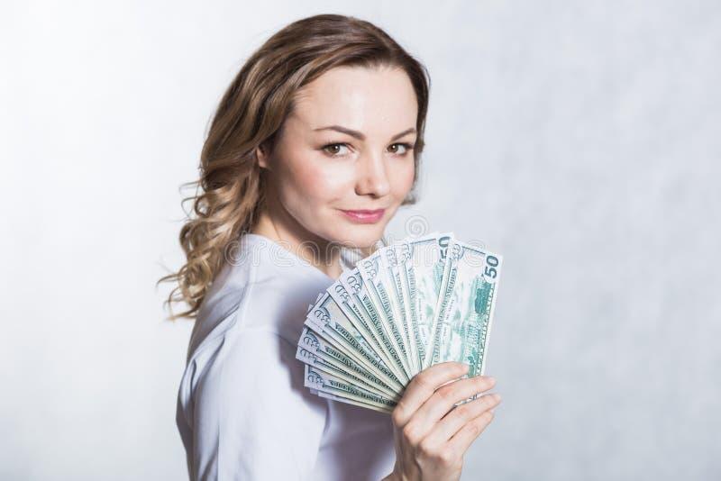 Gl?ckliche junge l?chelnde Frau in der Hand halten US-Dollar Geld ?ber wei?em Hintergrund lizenzfreie stockfotos