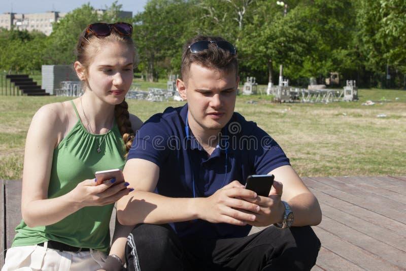 Gl?ckliche junge l?chelnde Paare des Portr?ts in der Liebe in bl?hendem Fr?hling arbeiten im Garten lizenzfreie stockfotos