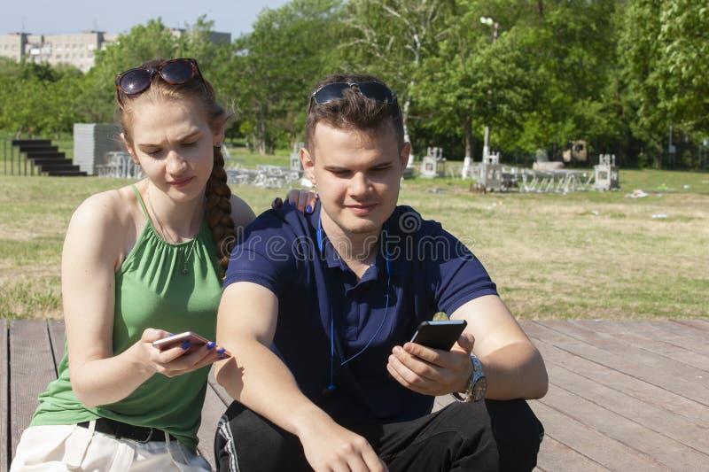 Gl?ckliche junge l?chelnde Paare des Portr?ts in der Liebe in bl?hendem Fr?hling arbeiten im Garten stockfotos
