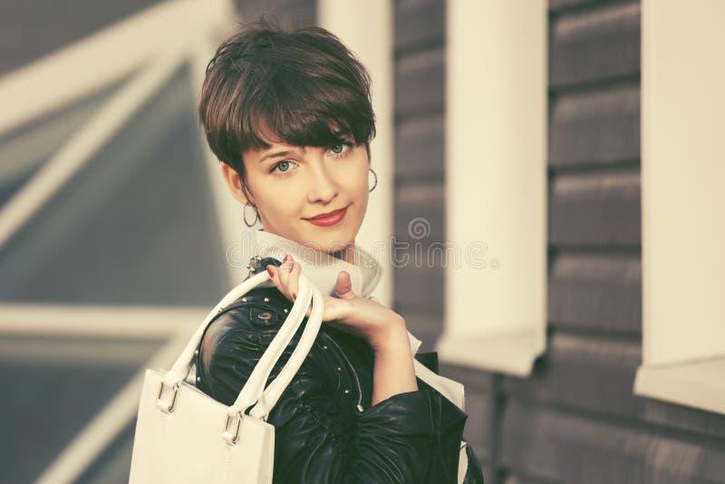 Gl?ckliche junge Modefrau in der Lederjacke mit Handtasche stockbild