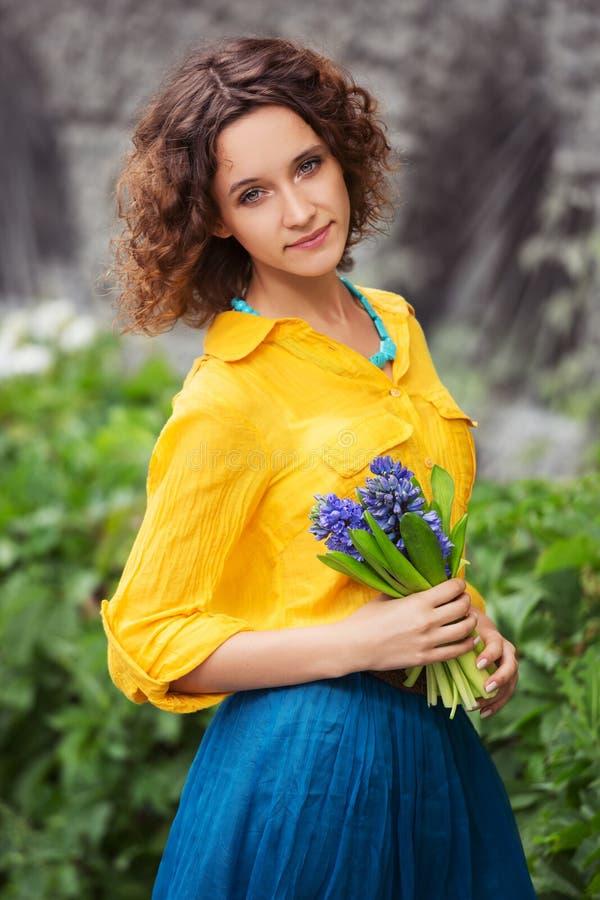 Gl?ckliche junge Modefrau im gelben Hemd mit Blumenstrau? von Blumen stockfotografie