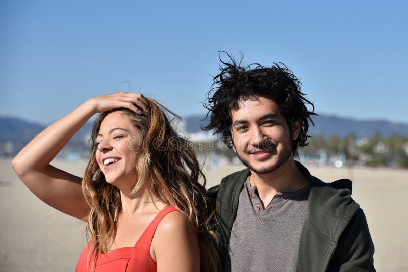 Gl?ckliche junge Paare auf dem Strand lizenzfreies stockbild