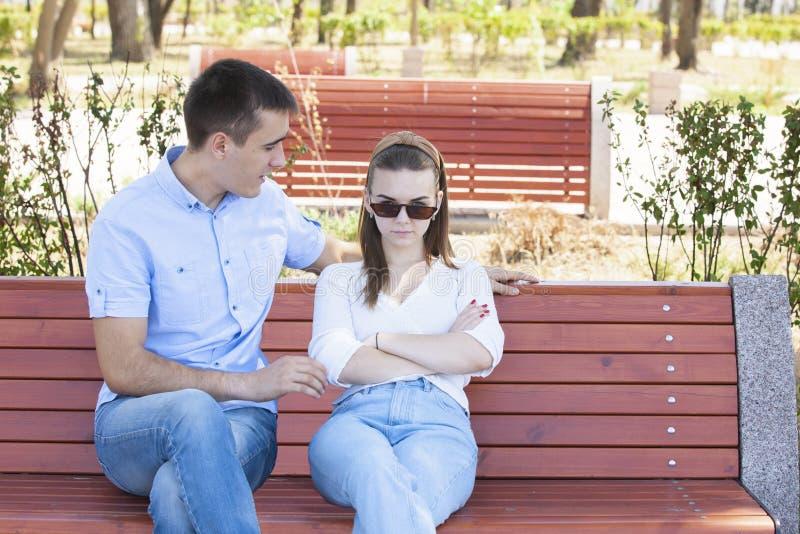 Gl?ckliche junge Paare in der Liebe, die auf einer Parkbank sitzt lizenzfreie stockfotos