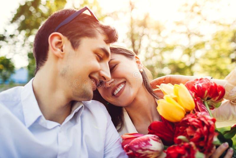 Gl?ckliche junge Paare in der Liebe, die drau?en mit Fr?hlingsblumenblumenstrau? umarmt Mann begabt seine Freundin mit Tulpen stockbilder
