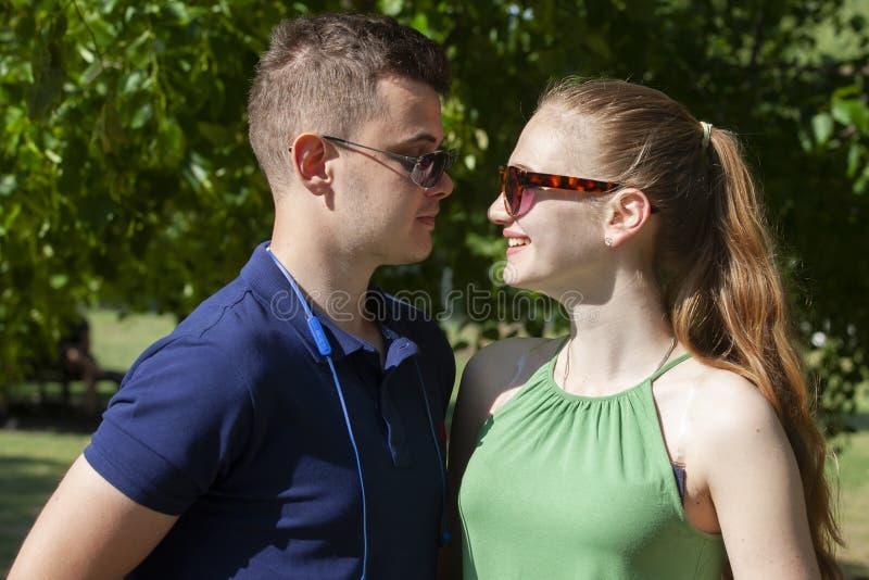 Gl?ckliche junge Paare, die drau?en umarmen und lachen stockbild