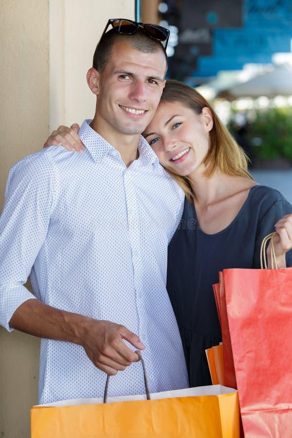 Gl?ckliche junge Paare mit Einkaufstaschen lizenzfreie stockbilder
