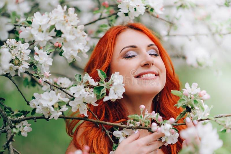 Gl?ckliche junge rothaarige Frau steht in bl?hendem Apfelgarten, Abschluss oben lizenzfreie stockfotos
