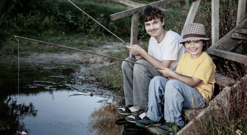 Gl?ckliche Jungen gehen, auf dem Fluss, zwei Kinder zu fischen des Fischers mit einer Angelrute auf dem Ufer von See lizenzfreies stockfoto
