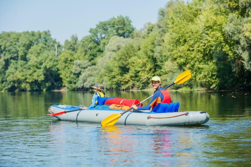Gl?ckliche Kinder, die auf dem Fluss an einem sonnigen Tag w?hrend der Sommerferien Kayak fahren stockbilder