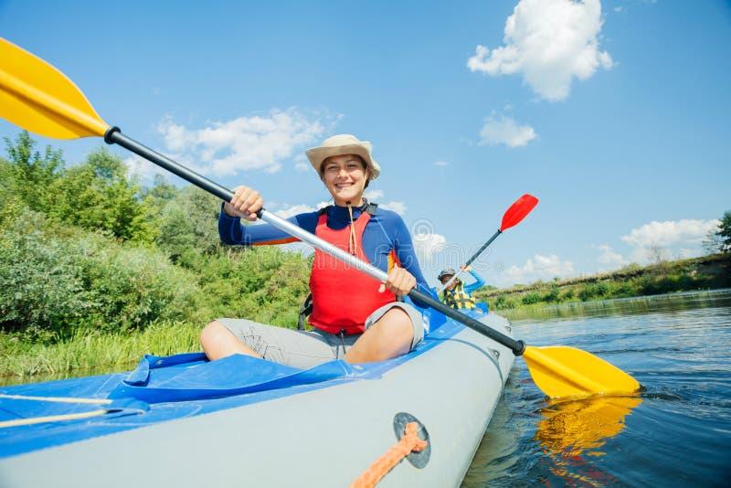 Gl?ckliche Kinder, die auf dem Fluss an einem sonnigen Tag w?hrend der Sommerferien Kayak fahren lizenzfreie stockfotografie