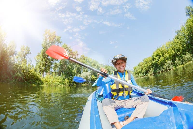 Gl?ckliche Kinder, die auf dem Fluss an einem sonnigen Tag w?hrend der Sommerferien Kayak fahren lizenzfreie stockbilder